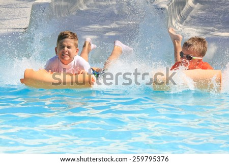 Faliraki,Rhodes,Greece-August,20,2015:Two young boys on the mat racer slide in Water park,Mat racer slide is very popular for young people in the Water Park. - stock photo