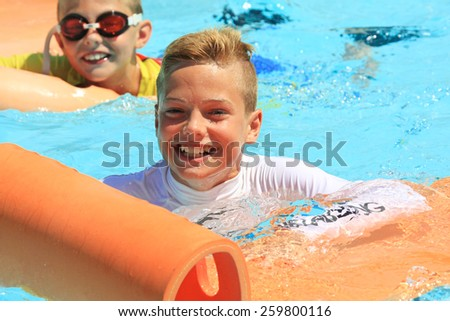 Faliraki,Rhodes,Greece-August,20,2015:Two young boys on the mat racer slide in Water park,Mat racer slide is very popular for young people in the Water Park - stock photo