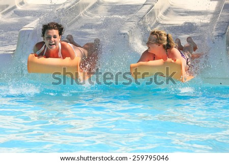 Faliraki,Rhodes,Greek-August,20,2015:Two young girls on the mat racer slide in Water park,Mat racer slide is very popular for young people in the Water Park - stock photo