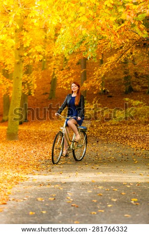 Fall active lifestyle concept,. Beauty young redhaired woman fashion girl relaxing in autumn park with bicycle, outdoor