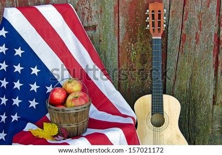 fall apples with leaves on American flag with guitar by old weathered barn - stock photo