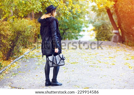 Fall autumn fashion image of stylish woman in trendy parka jacket lather pants and vintage hat walking alone at amazing countryside park, beautiful gold yellow trees. - stock photo