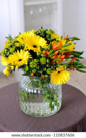Fall  bouquet with gerbera daisies and decorative peppers in a vase
