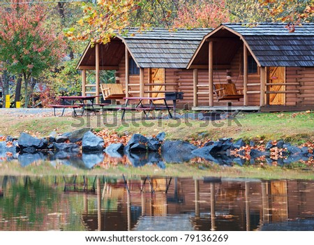 Fall colors of the trees and a cabin reflecting in the water of a small lake in North Carolina, USA. - stock photo