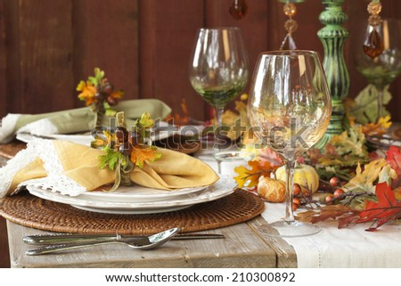 Fall dining place settings on rustic table and dark red wall - stock photo