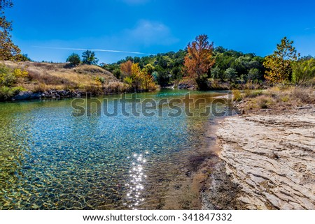 Fall Foliage on a Crystal Clear Creek in the Rural Back Roads of the Hill Country of Texas. - stock photo