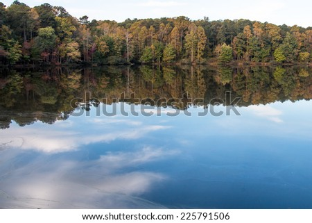 Fall foliage with blue sky and clouds reflected on lake - stock photo