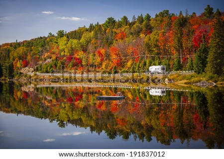 Fall forest with colorful autumn leaves and highway 60 reflecting in Lake of Two Rivers.  Algonquin Park, Ontario, Canada. - stock photo