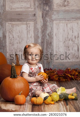 Fall Fun!  Adorable baby girl surrounded by pumpkins and gourds and other fall decor in the background.   - stock photo