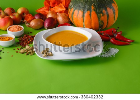 Fall harvesting concept. Pumpkin soup with onion and pepper on green shadowless background