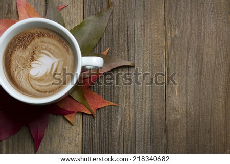 Fall latte sitting on wooden table with fall leaves - stock photo