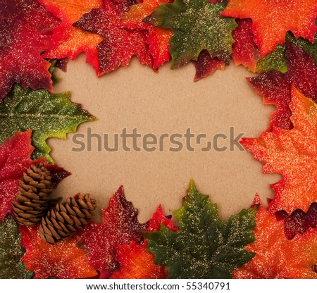 Fall leaves making a border with a pinecone on a beige background, fall border - stock photo