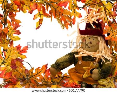 Fall leaves with a scarecrow isolated on white, autumn border - stock photo