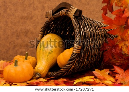 Fall leaves with pumpkins and gourds in basket on brown background, fall harvest frame - stock photo