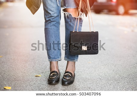 fall outfit fashion details, young stylish woman wearing ripped jeans and black loafers. fashion blogger holding a trendy black purse with a golden chain.