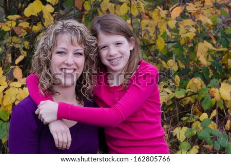 Fall portrait of a mother and her pre-teen daughter with room on the side left for text - stock photo