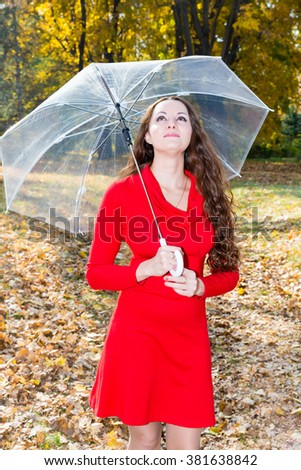 Fall. Portrait of beautiful young woman in autumn park with maple leaves