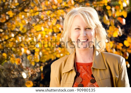 Fall portrait of happy middle-aged blonde woman - stock photo