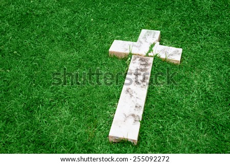 Fallen and broken down marble cross resting on a green grass - stock photo