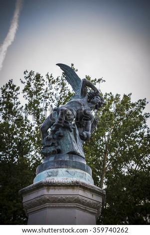 fallen angel, devil figure, bronze sculpture with demonic gargoyles and monsters - stock photo