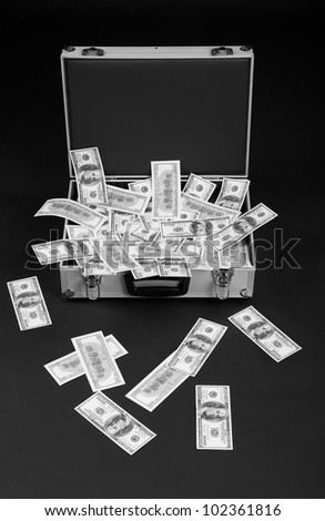 fallen money from full suitcase on a black background - stock photo