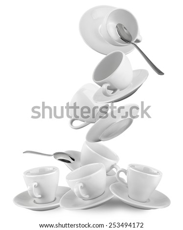 falling cups and saucers with spoons isolated on white - stock photo