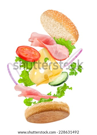 falling delicious sandwich with ingredients: ham, cheese, tomato, cucumber, onion, lettuce - stock photo