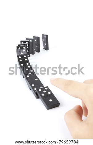 falling dominos, dominos arranging in line and hand fall them down. - stock photo