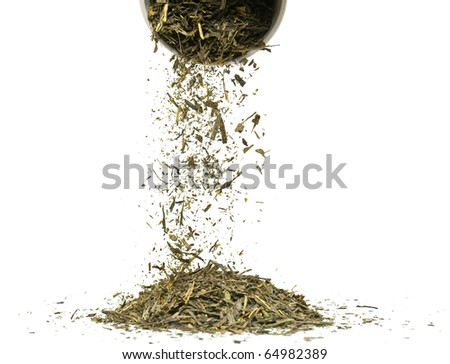 Falling dried green tea leaves over white background - stock photo