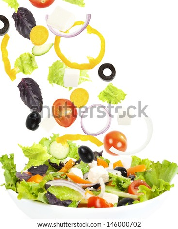 Falling fresh vegetable on plate with salad - stock photo