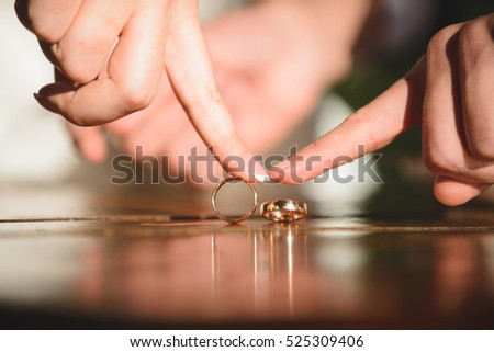 falling ring under groom's finger and bride with ring