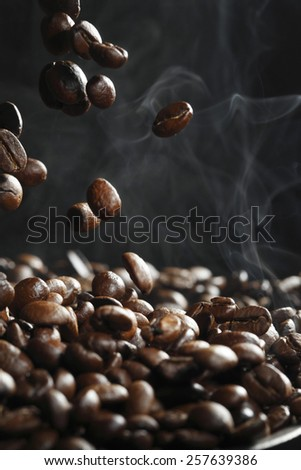 Falling roasted coffee beans with steam on black - stock photo