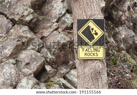 Falling rocks sign on tree with rocky background - stock photo