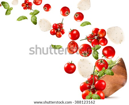 Falling salad in a wooden salad bowl. Tomato, mozzarella and basil isolated on white background - stock photo