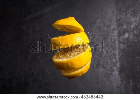 Falling slices of lemon in air on black background
