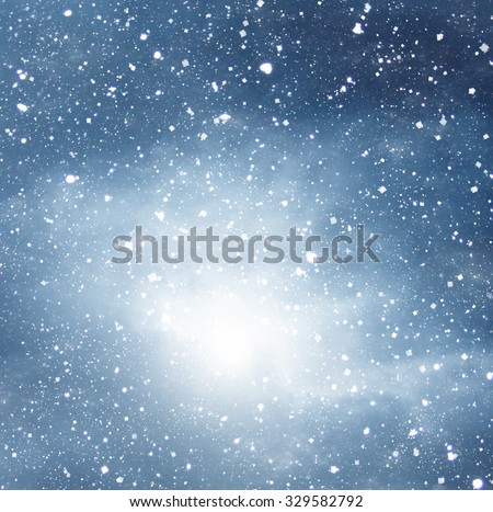 falling snow on the blue background dramatic dark sky background - stock photo
