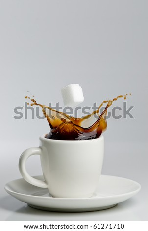 Falling sugar cube into splashing black coffee in white cup.