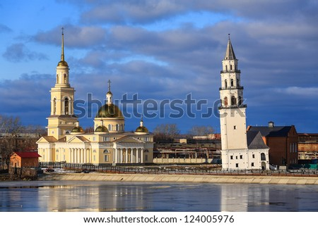 Falling tower in Nevyansk and church - stock photo