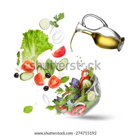 Falling vegetables for salad and olive oil isolated on white
