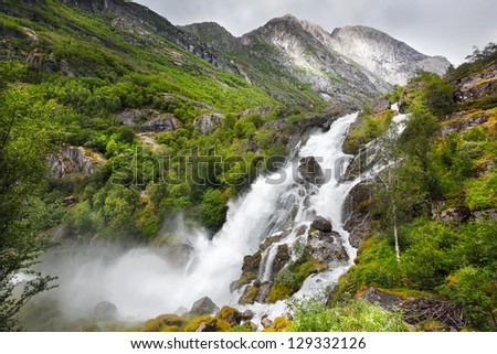 Falls in mountains of Norway in rainy weather. - stock photo