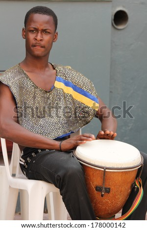 FALMOUTH, JAMAICA � MAY 11: An unidentified street performer playing outside the port of Falmouth on MAY 11, 2011 in Jamaica ahead of the national labor day celebrations. - stock photo