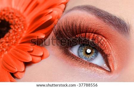 false eyelashes and fashion eye make-up with  orange flower - stock photo