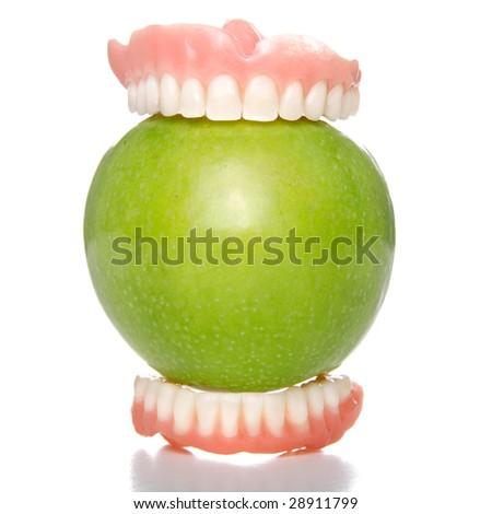 False teeth having a big bite into a green apple - stock photo