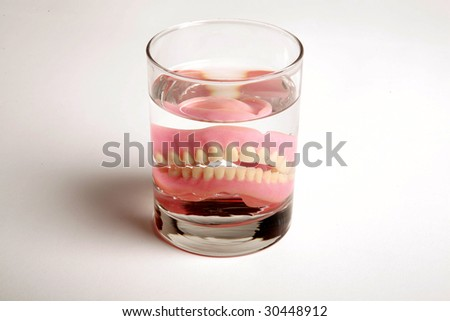 False Teeth in a glass of water - stock photo