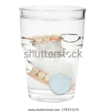 """False Teeth in a glass with cleaning tablets and water glass """"isolated on white"""" - stock photo"""