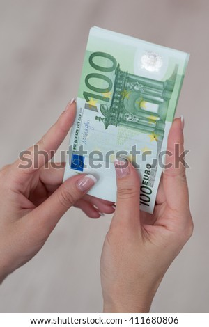 Famale hand holding several euro money banknotes. - stock photo