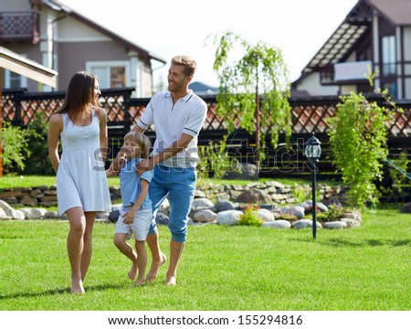 Families with a child on a lawn - stock photo