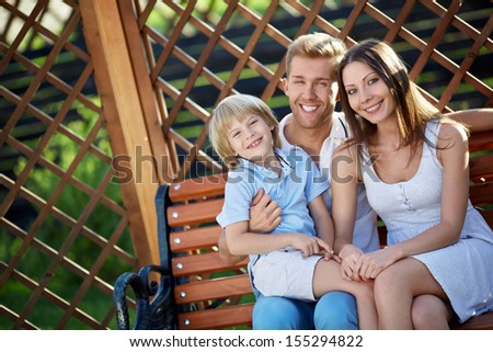 Families with a child on a wooden bench - stock photo