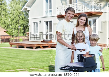 Families with children against the house with a barbecue - stock photo