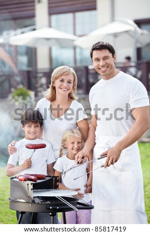 Families with children with barbecue outdoors - stock photo